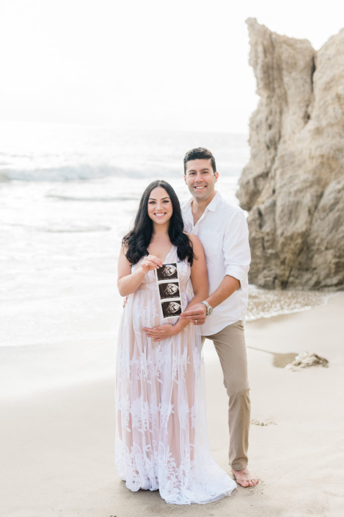 pregnancy announcement, couple standing in front of the ocean holding a sonogram